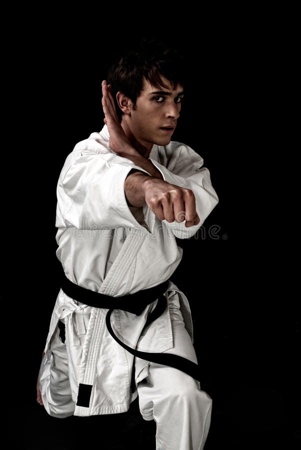 High Contrast karate young male fighter on black. Background stock photos