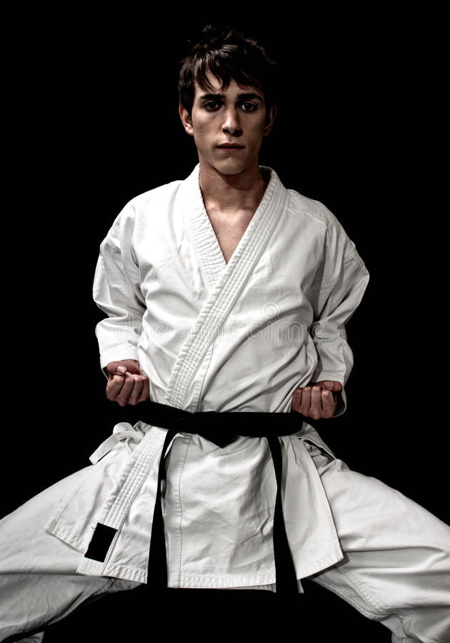 High Contrast karate young male fighter on black. Background stock photography