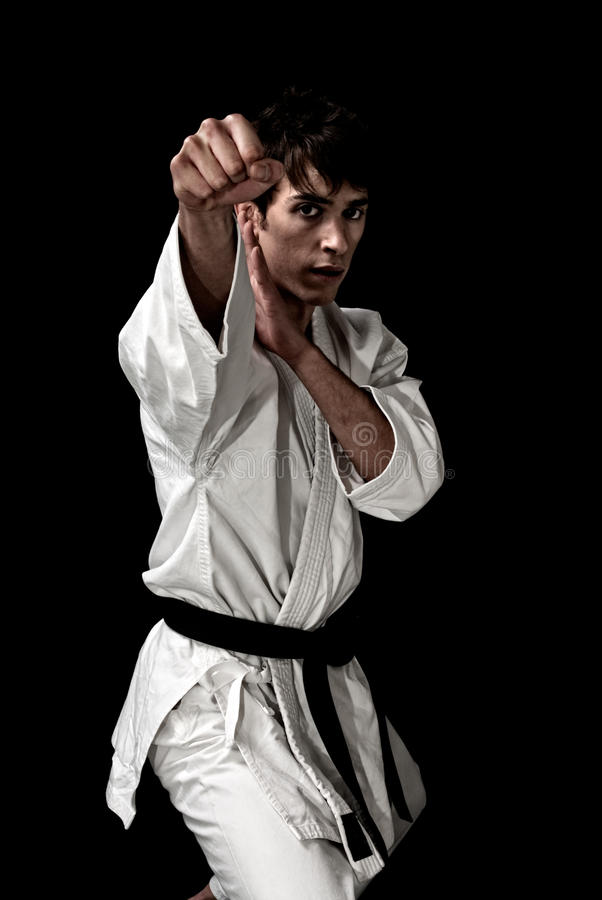 High Contrast karate young male fighter on black royalty free stock photography