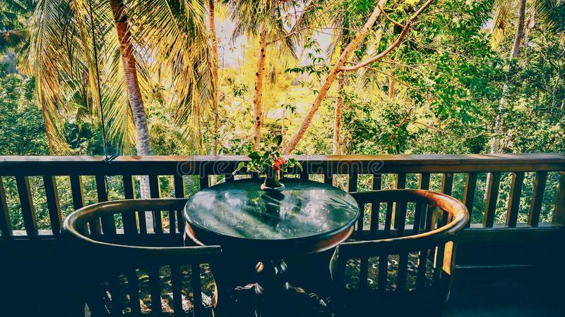 A table for two on a balcony overlooking a tropical jungle in Bali. royalty free stock photos