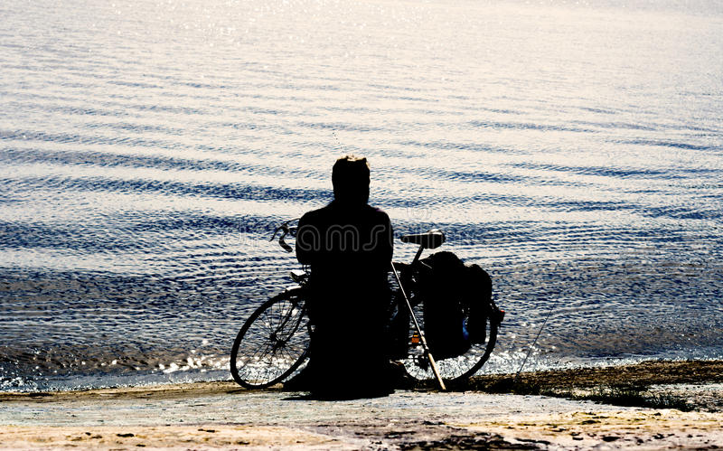 High contrast styled fisherman silhouette with retro bicycle on the beach. With fishing rod stock images