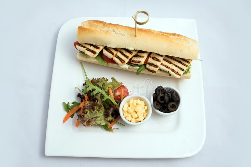 A high contrast vertical Hero shot of a Grilled Halloumi cheese baguette with olives & salad on the side, on a minimal white royalty free stock image