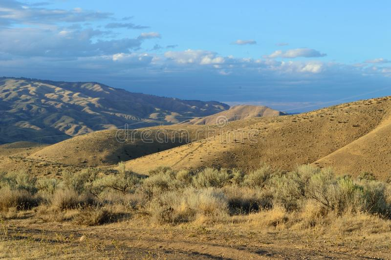 High Desert Hills Stratus Clouds Breathtaking Idaho Landscape. Golden Hour with stratus clouds in blue sky over the high desert foothills at Bonneville Point stock image