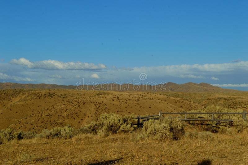 High Desert Hills Stratus Clouds Idaho Landscape. Golden Hour with stratus clouds in blue sky over the high desert foothills at Bonneville Point Route of the royalty free stock photo