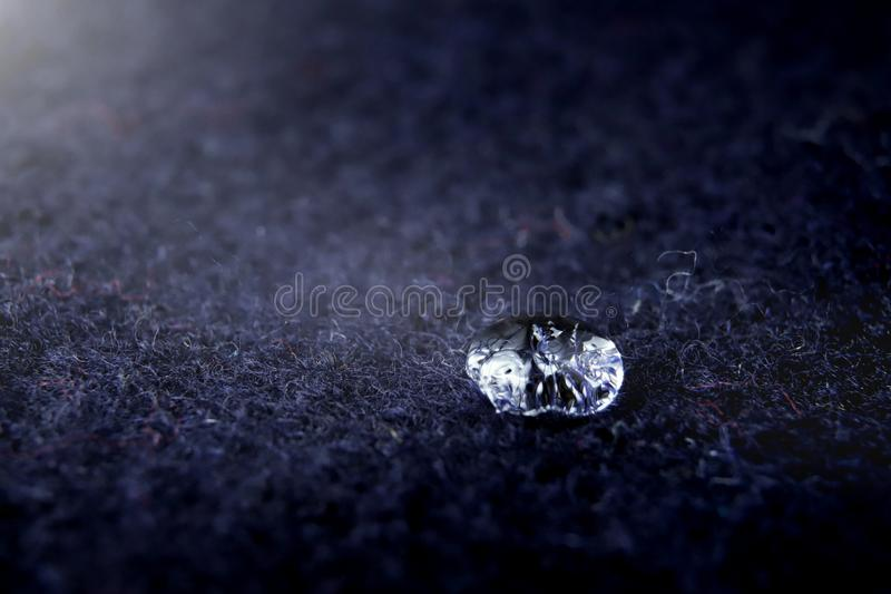 high detail close-up of sparkling drop of water on dark blue boild wool - bright light mood with deep shadows royalty free stock photos