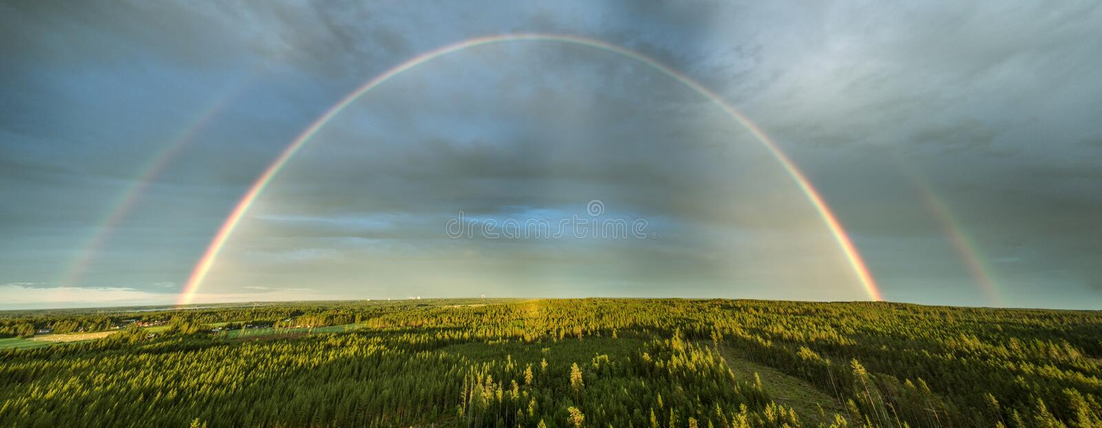 High detailed drone panorama of double rainbow over summer pine tree forest, very clear skies and clean rainbow colors. This photo. Stitched from 6 shots royalty free stock image