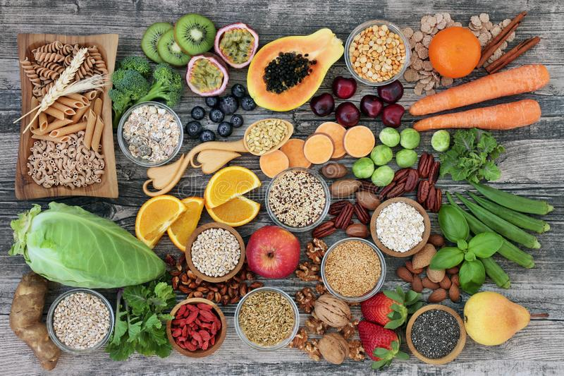 High Dietary Fiber Health Food. High dietary fibre health food concept with fruit, vegetables, whole wheat pasta, legumes, cereals, nuts and seeds with foods stock photos