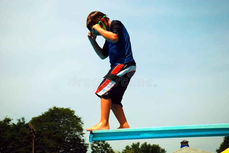 On the High Dive. A Young Boy Prepares to go off the high diving board stock images