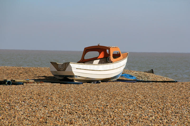 High and Dry. A small dingy high and dry on the pebbles of Southwold beach royalty free stock photo