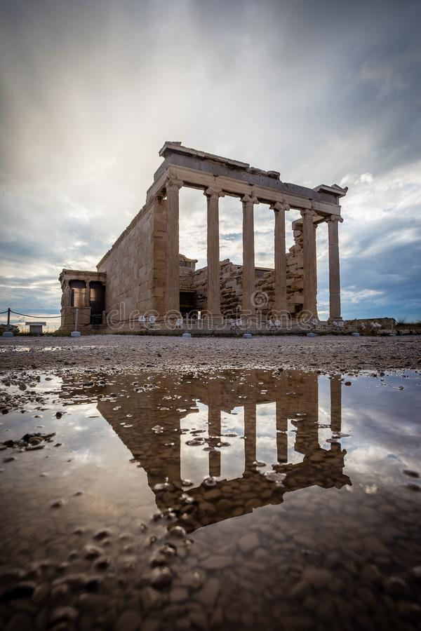 High dynamic range photo of Temple of Athena in Acropolis, seen with reflection on puddle and dramatic sky.  royalty free stock photo