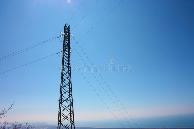 High electricity tower as opposed to the blue sky. In the natural park of the apennines. telecommunication and communication system royalty free stock photo