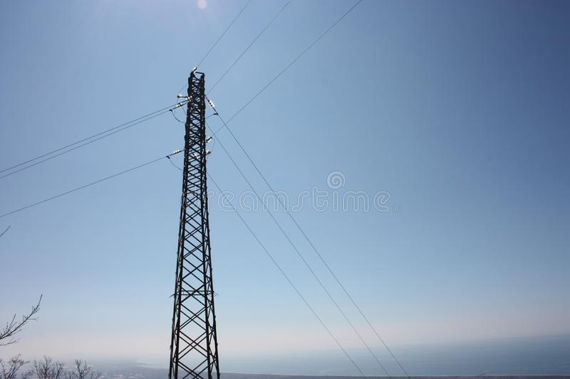 High electricity tower as opposed to the blue sky. Telecommunication system royalty free stock image
