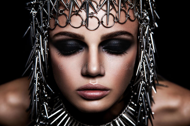 High fashion beauty model with metallic headwear and dark makeup and blue eyes on black background.  stock photos