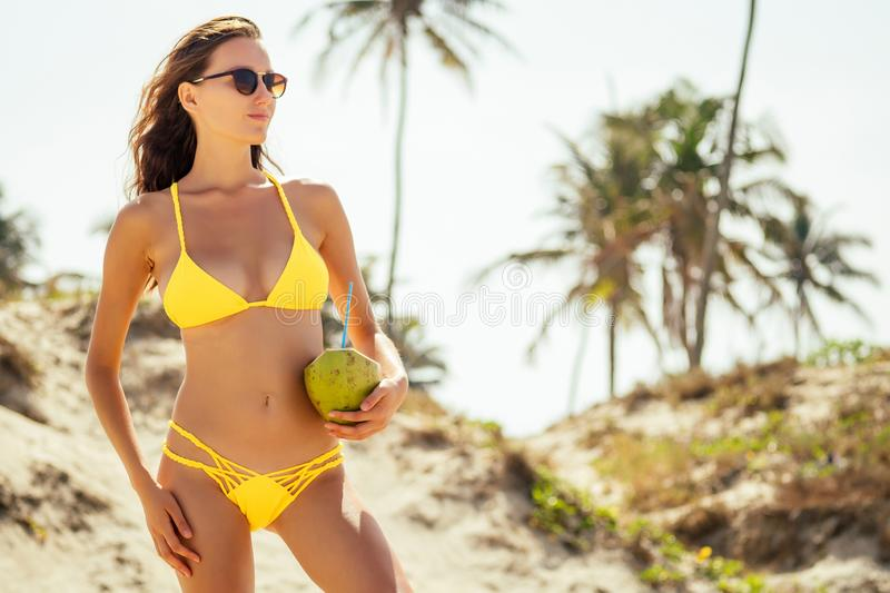 High fashion look.glamor beautiful sexy stylish young woman model perfect sunbathed clean skin in yellow swimsuit posing. On the beach on sea vogue style stock images