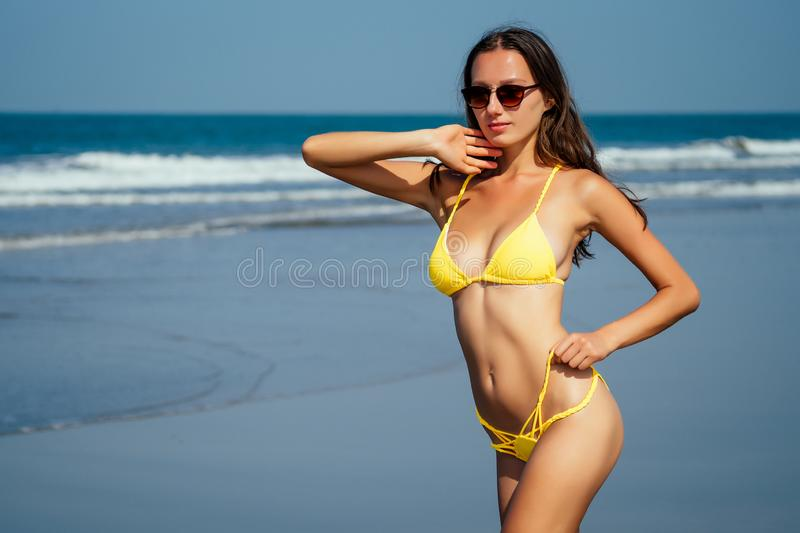 High fashion look.glamor beautiful sexy stylish young woman model perfect sunbathed clean skin in yellow swimsuit posing. On the beach on sea vogue style royalty free stock images