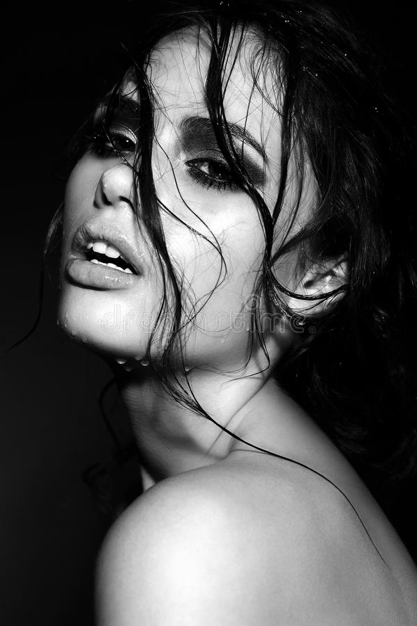 sensual brunette model with wet skin with curly hair stock images