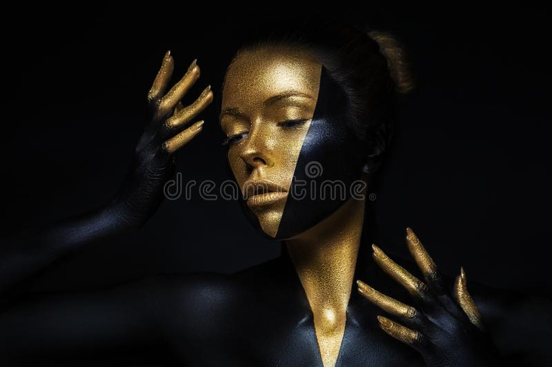 High fashion model with black and gold leather, golden fingers. Isolated on black background Beauty female face, creative make-up royalty free stock images