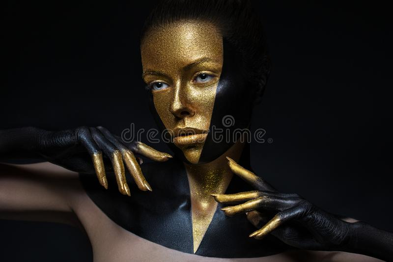 High fashion model with black and gold leather, golden fingers. Isolated on black background Beauty female face, creative make-up royalty free stock photo