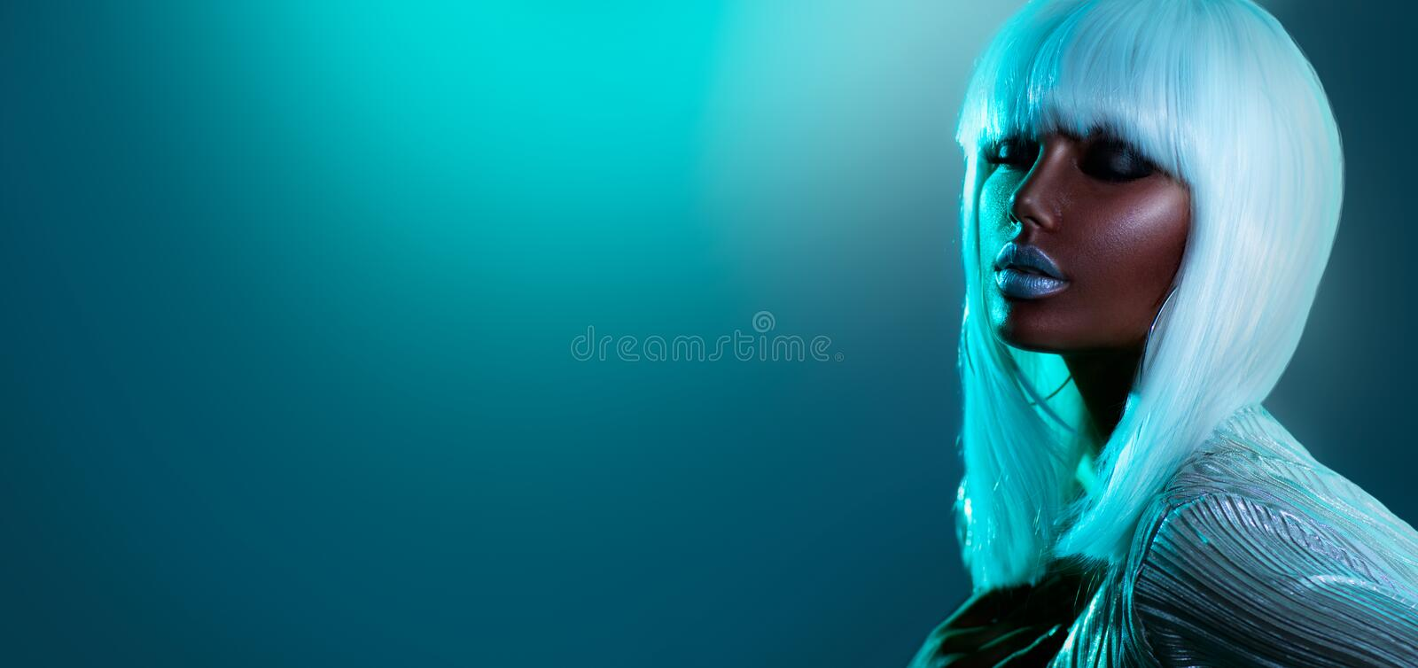 High Fashion model girl in colorful bright neon lights posing in studio, portrait of beautiful African American woman in white hai stock photo