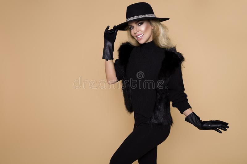 High fashion Model girl portrait on beige background. Beauty stylish blonde woman posing in fashionable clothes in studio. Casual style, beauty accessories.Hat stock photography