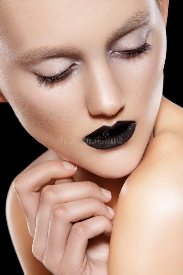 High fashion model. Make-up trend, rock black lips. High fashion beauty portrait of glamour model with luxury make-up & black lips on black background royalty free stock image
