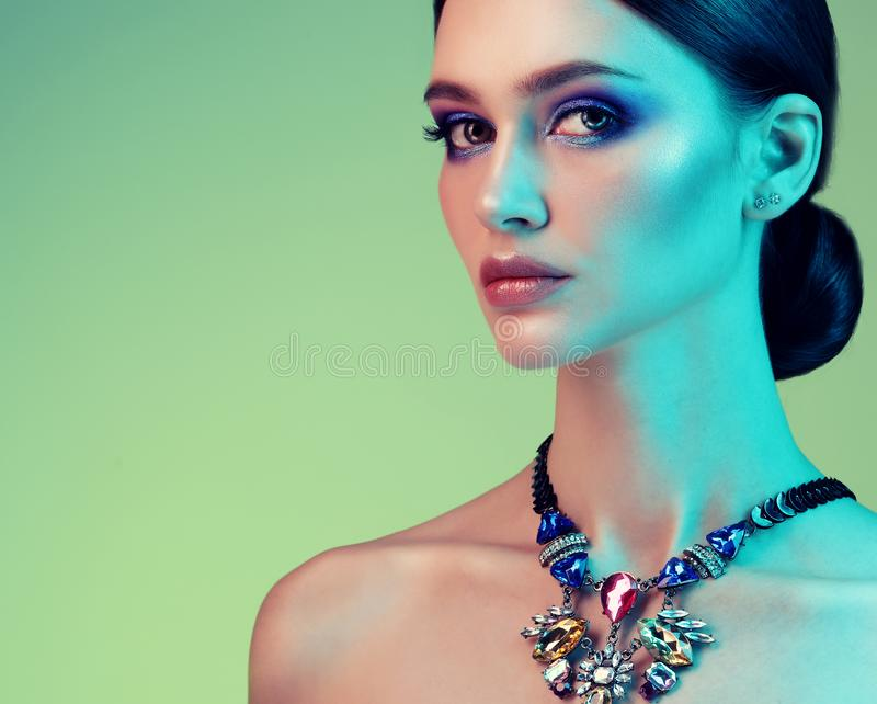 High Fashion model woman posing in studio. Portrait of beautiful sexy girl wearing jewelry with trendy make-up stock images