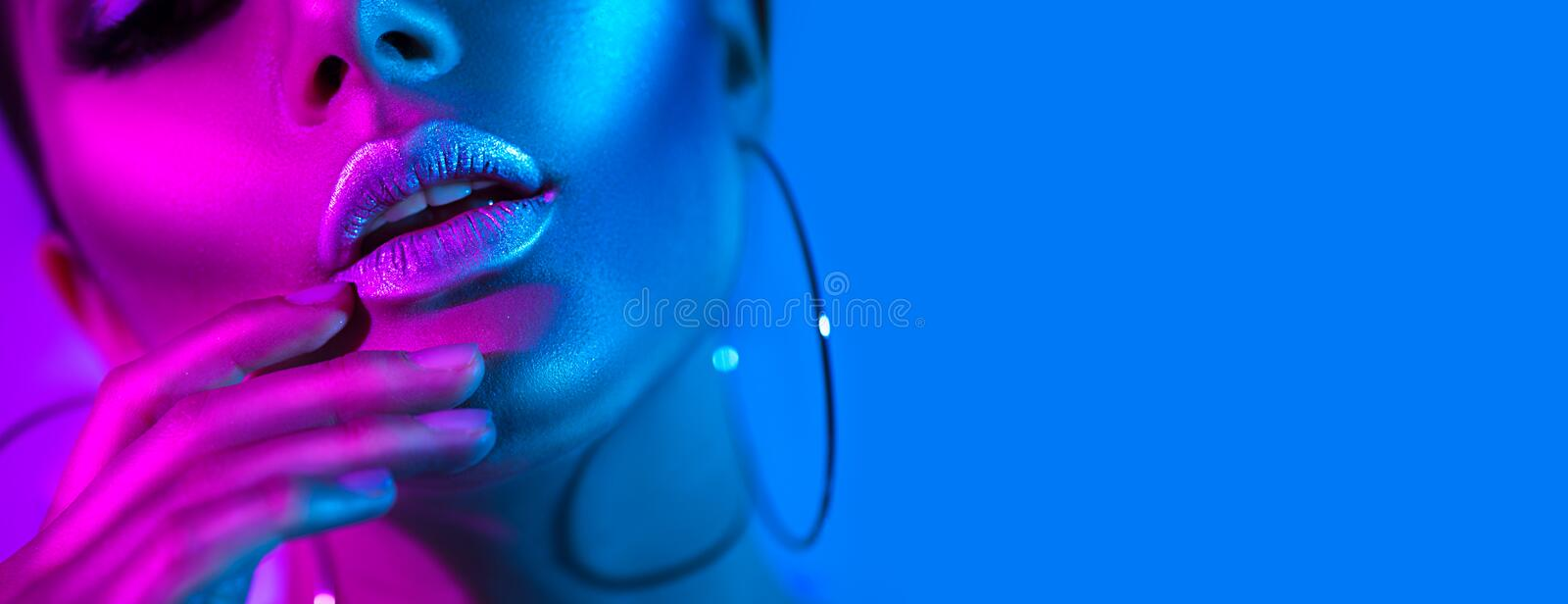 High fashion model woman in colorful bright neon lights posing in studio. Beautiful girl royalty free stock image