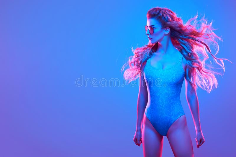 High Fashion neon light.Sexy Girl,Trendy Hairstyle. High Fashion Model in colorful bright neon blue and purple lights. Glamour Girl with Trendy Wavy Hairstyle stock photo