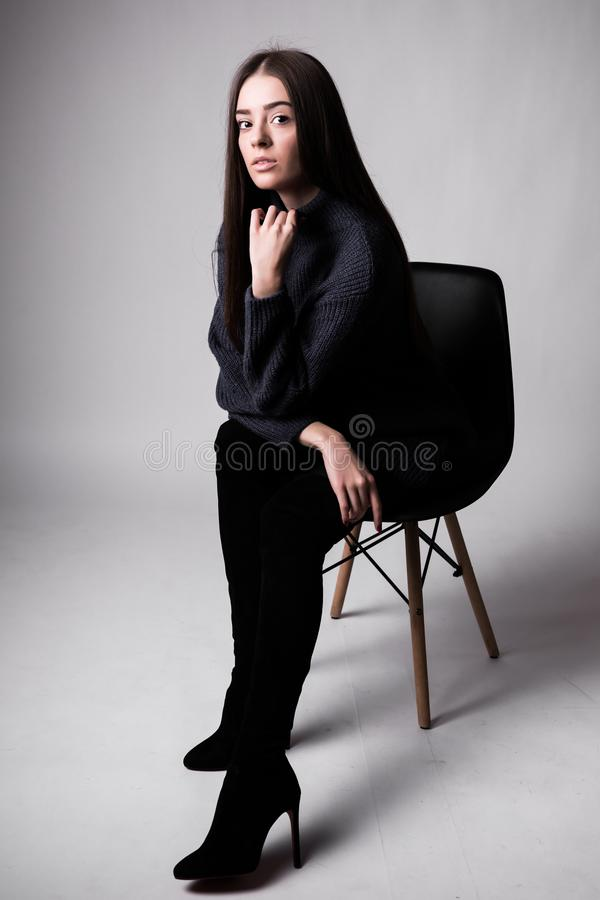 High fashion portrait of young elegant woman sittung on chair black clothes isolated on white background stock images