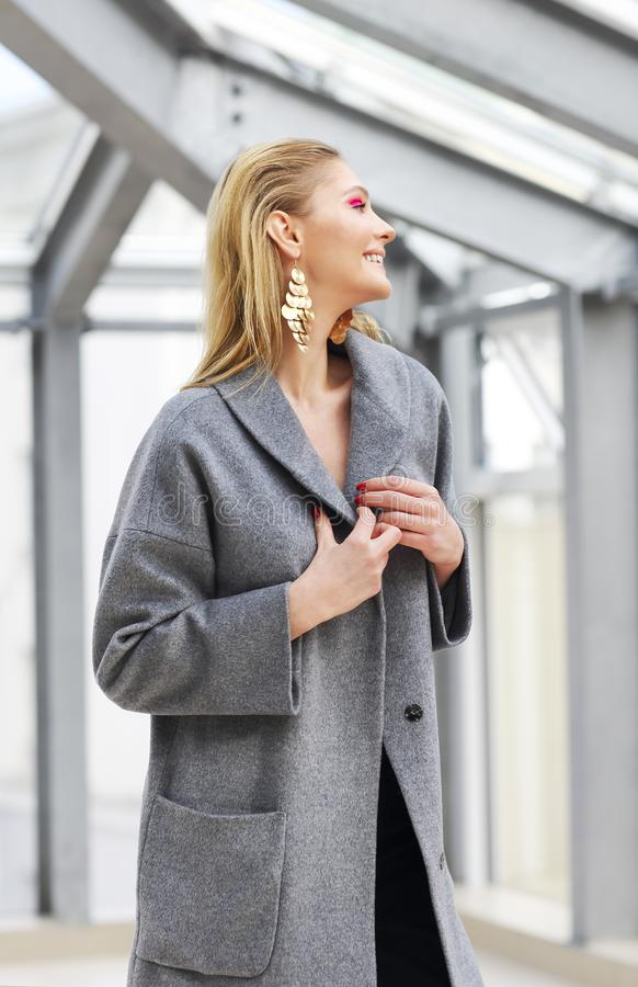 Fashion portrait of young elegant woman in Grey coat, black pants, black ankle boots and gold earrings. High fashion portrait of young elegant woman in Grey coat royalty free stock image