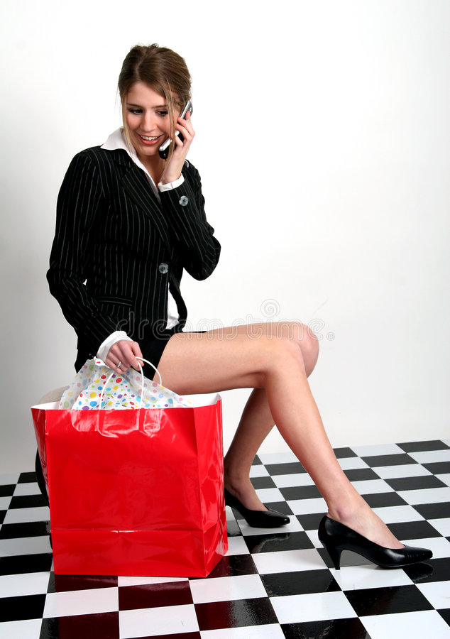 High-fashion shopper. Beautiful young woman in business suit talking on cell phone with red shopping bag next to her. Young woman talking on the cellphone while stock photos