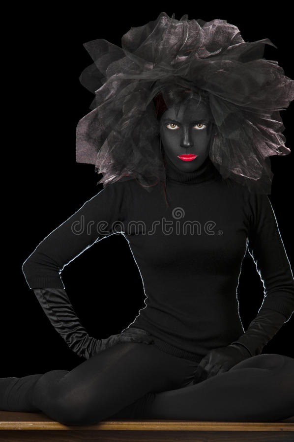 High Fashion Shot - Black Face. Photo of a high fashion model, with black painted face and sitting cross-legged. She has a black accessory on her hair, made of stock image