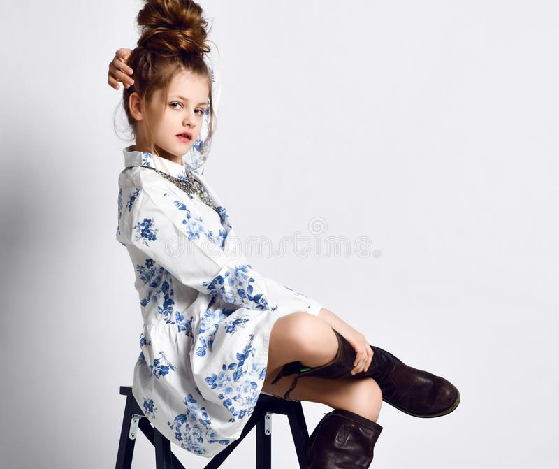 High fashion teen girl kid in modern summer dress with blue flowers, necklace and big black boots sitting posing on stepladder. High fashion teen girl kid in stock image