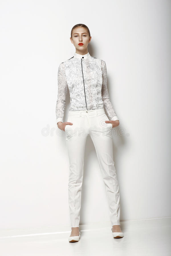 High Fashion. Trendy Woman in White Breeches in Graceful Pose. Spring Time Collection. Woman in pants in Graceful Pose. Spring Time Collection stock images