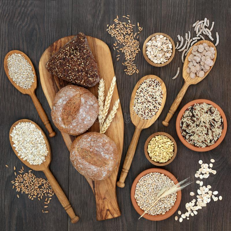 High Fiber Health Food. Concept with fresh whole grain bread rolls, cereals and grains. Rustic background on oak, top view royalty free stock photos