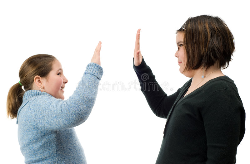 High Five. Two young girls giving each other a high five with their hands, isolated against a white background royalty free stock photo
