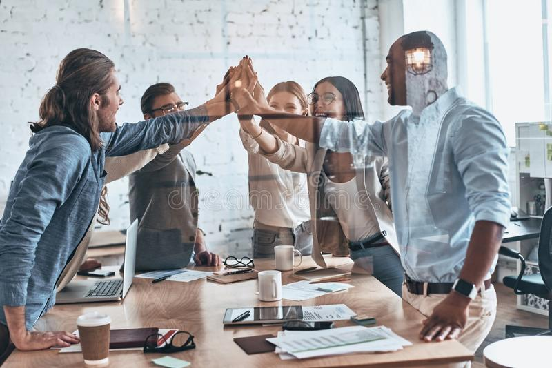 High-five! Group of business colleagues giving each other high-five while working behind the glass wall in the board room stock photo