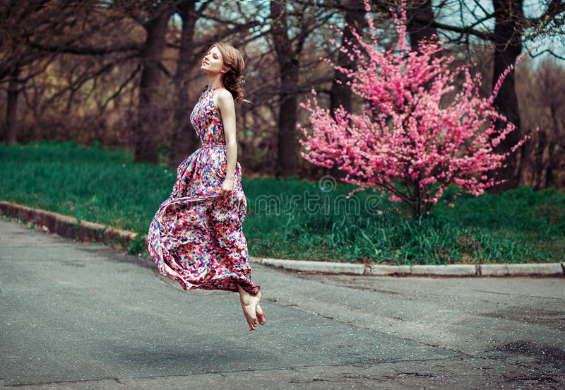 High flying success and joy for happy slim young woman wearing long dress, jumping into the air outdoors in countryside stock image