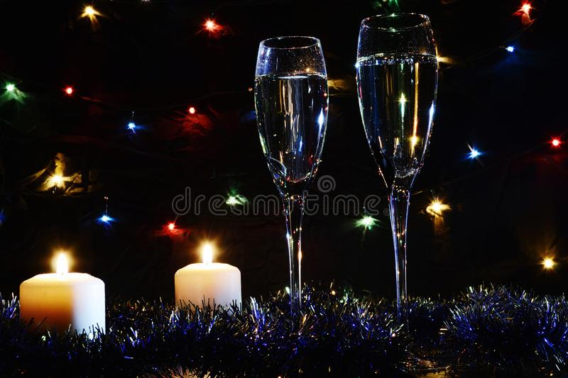 High glasses for champagne. Good New Year spirit. Candles and ch stock photography