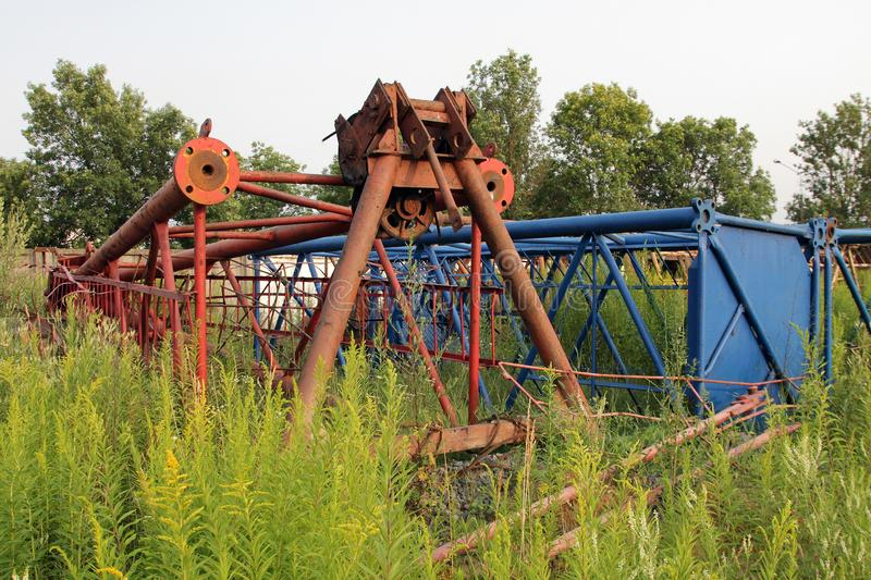 The high grass grows around the iron fragments of tower cranes stock images