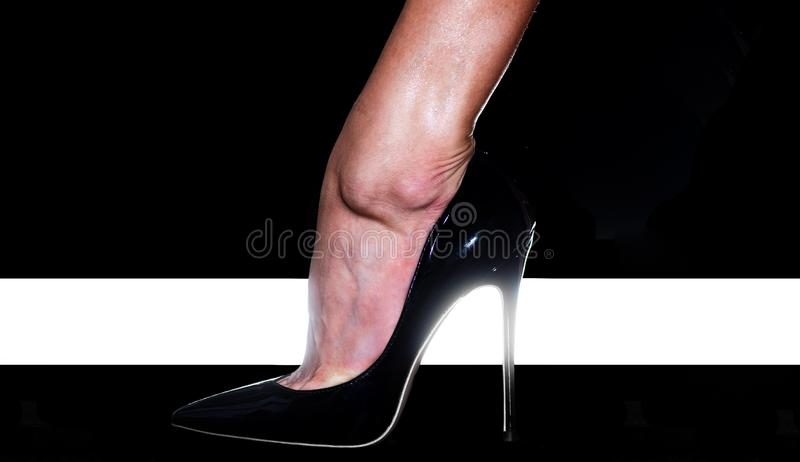 High heel. Fashion. Female foot in a black shoe. High Fashion Week. High rise of the foot. Elegant female legs. Fashionable patent leather shoes stock photos