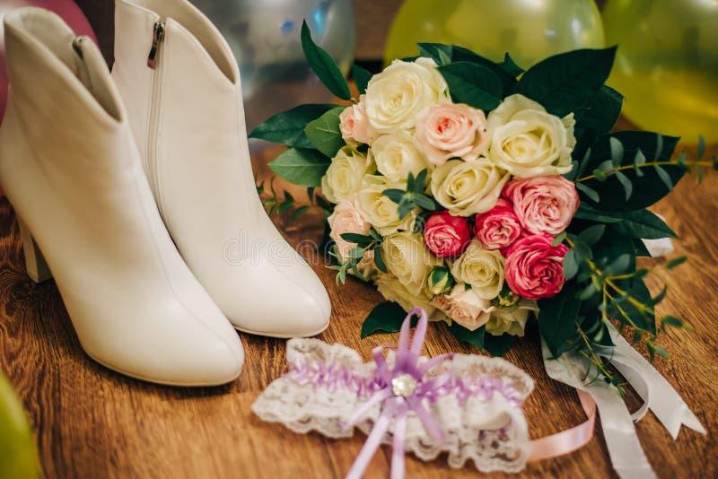 High-heeled schoenen van de wintervrouwen ` s met een verband op de voet en een huwelijksboeket voor de bruid stock afbeelding