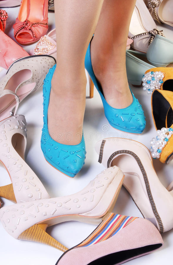 High-heeled shoes. Female legs in high heels and a number of different high-heeled shoes stock image