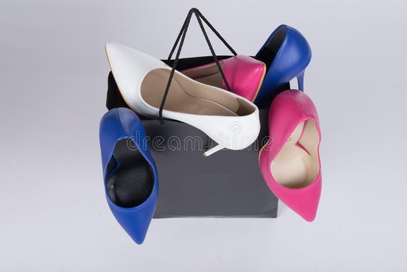 High-heeled stiletto schoen-gevulde het winkelen zak en het overlopen op geïsoleerde achtergrond royalty-vrije stock foto's