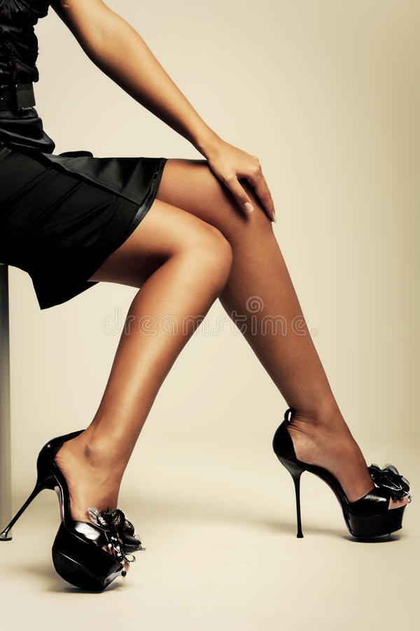 High heels. Beautiful tanned female lags in high heels, studio shot royalty free stock image