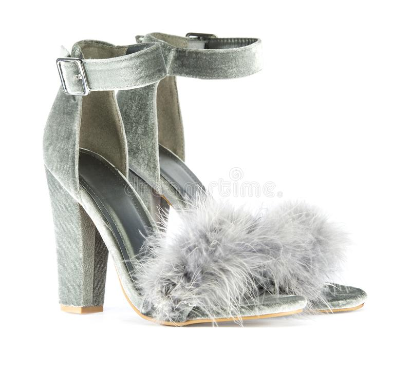High heels with faux fur in gray. High heels shoes with ankle strap and fancy faux fake fur in gray suede, isolated on white background royalty free stock photography