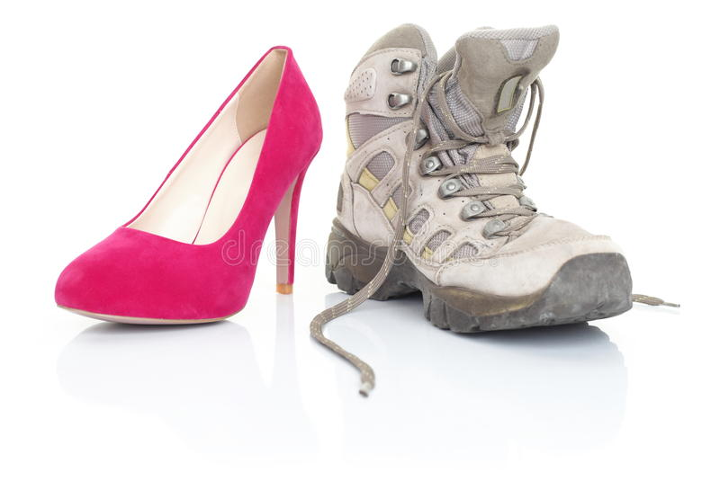 High heels and hiking shoes on white royalty free stock image
