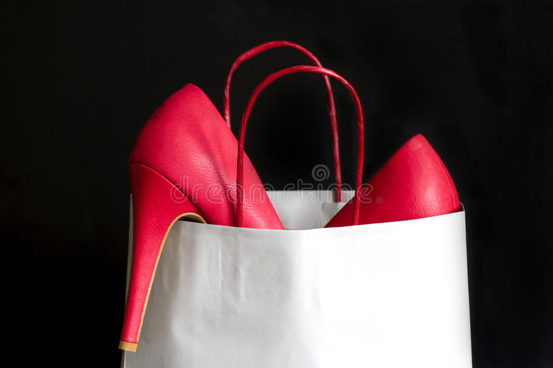 High heels red shoes in shopping bag royalty free stock images