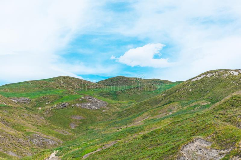 High hills with green grass blue sky with clouds.  stock photos