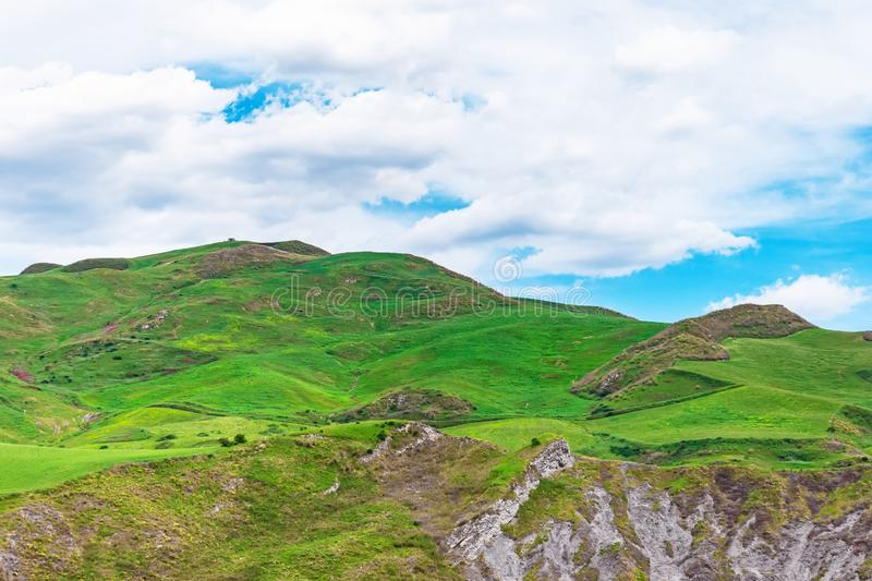 High hills with green grass blue sky with clouds.  royalty free stock photography